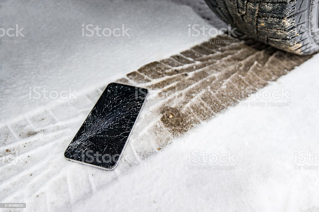 Phone with broken screen on snow in car trails stock photo