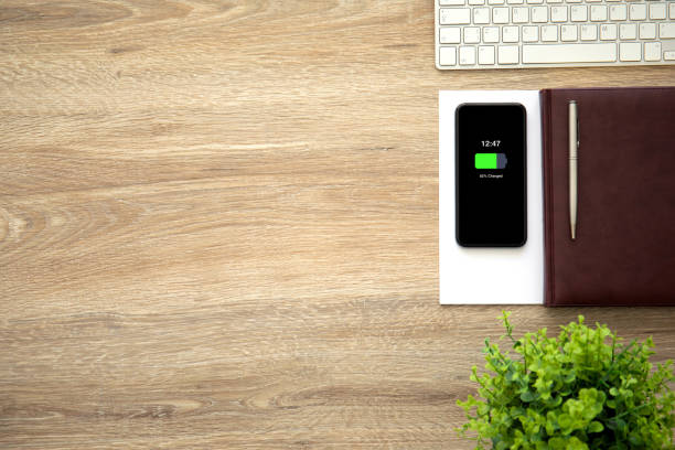 telefon mit aufgeladener batterie auf dem bildschirm notebook und tastatur - sinnvolle wörter stock-fotos und bilder