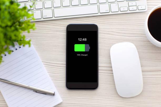 telefon mit geladener batterie bildschirm auf tisch im büro - sinnvolle wörter stock-fotos und bilder