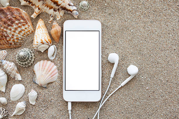 phone with isolated screen and headphones on the sand stock photo