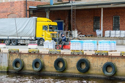 Karlshamn, Sweden - May 06, 2015: Unknown male forklift driver making a phonecall while unloading pallets at the docks. Truck and building in background.