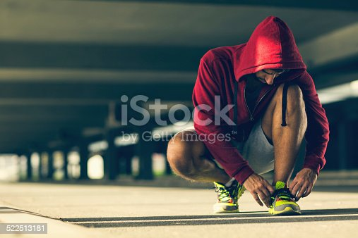 istock Photo af an athletic man tying his shoelace 522513181