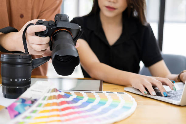 Photo artist and graphic desginer selecting pictures from camera. stock photo