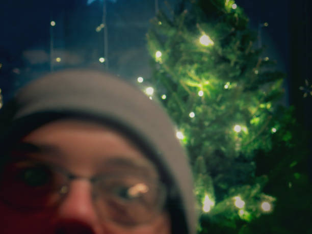 Photo Bomber Wearing Glasses and Hat in front of Christmas Tree stock photo