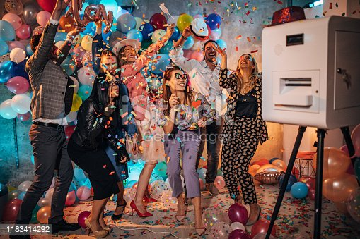 Group of young women and men having fun with balloons and photo booth at a party