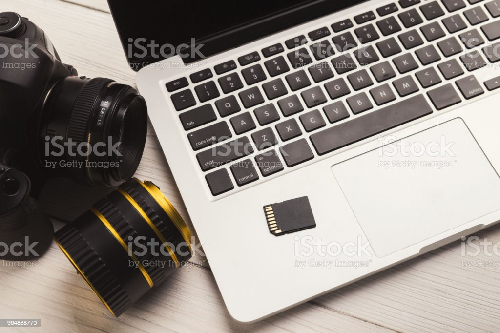 Photo camera, lens and memory card on computer royalty-free stock photo