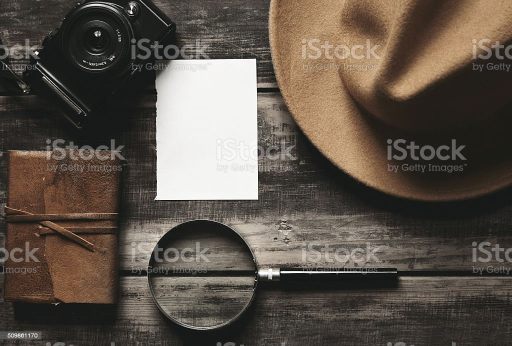 Photo camera, notebook, hat, magnifier, paper on black table stock photo