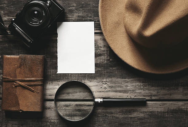 Photo camera, notebook, hat, magnifier, paper on black table Mysterious detective game concept. Closed notebook in leather cover, sheet of white paper, felt brown hat, portable mirrorless microthird digital photo camera and big vintage magnifier isolated on black aged wood table detective stock pictures, royalty-free photos & images