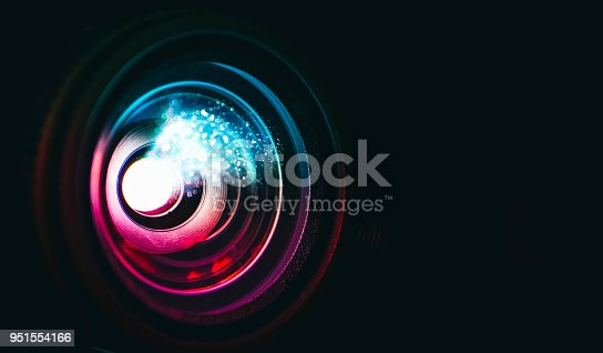 Photo depicts digital projector film presentation. Projector shiny colorful glass lens closeup, macro view, black background.