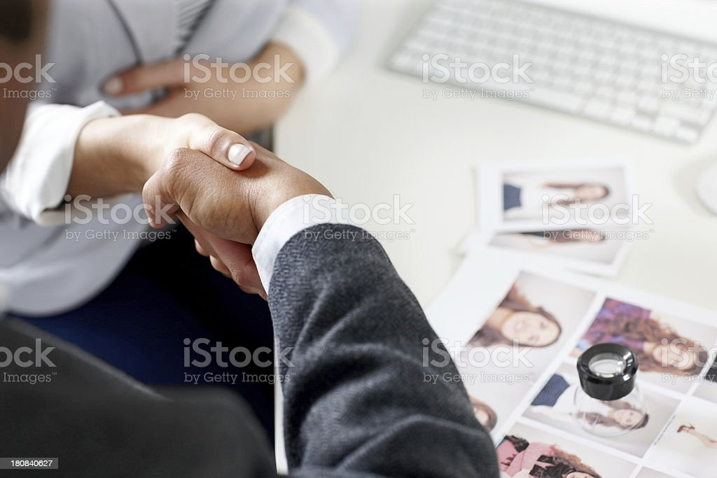 Photo editors shaking hands at their work desk royalty-free stock photo