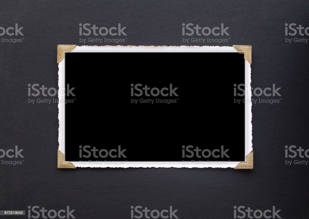 Photo frame - real old photo with black blank space for copy photo pasted with gold coloured photo holder corners onto black vintage album paper page - Photograph stock photo