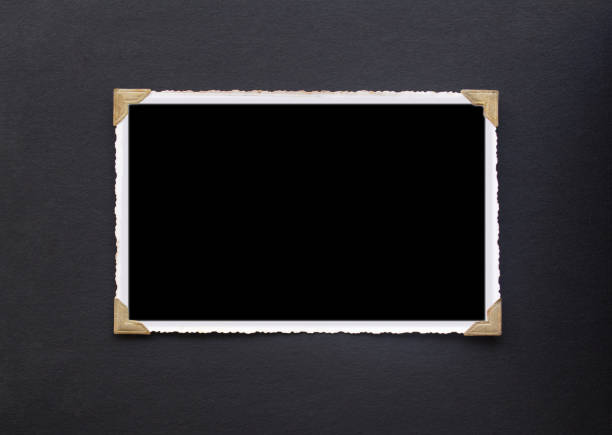photo frame - real old photo with black blank space for copy photo pasted with gold coloured photo holder corners onto black vintage album paper page - photograph - photo corner stock photos and pictures