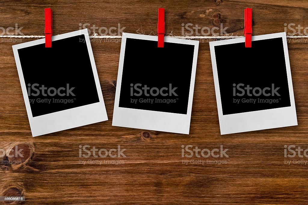 Photo frames hanging on red clothespins. Wooden background stock photo