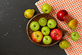 istock Photo from above - apples and pears in wooden carved bowl on black marble like working desk with tablecloth 1143723287