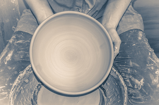 Photo in old vintage style. Master Potter holds half round clay plate