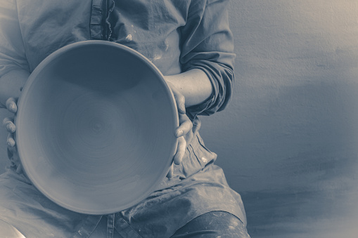 Photo in old vintage style. Potter holds round clay plate in his hands.