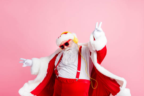 Photo modern funky santa claus listen x-mas christmas stereo radio use headphones raise hands fingers wear style stylish big belly costume pants headwear isolated pastel color background stock photo