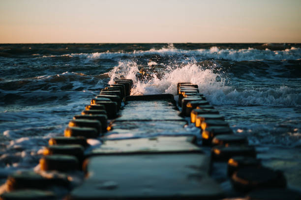 photo of a beach waves and a wooden deck stock photo