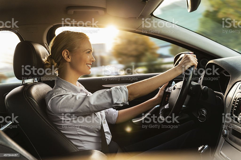 Photo of a beautiful smiling young businesswoman driving car stock photo