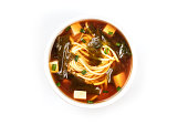 A photo of a bowl of miso shiru soup with tofu, scallions, noodles, and wakame seaweed, shot from the top on a white background with copy space
