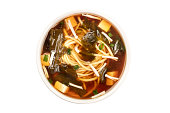 A photo of a bowl of miso soup with tofu, scallions, noodles, wakame, and enoki mushrooms, shot from the top, isolated on a white background with a clipping path