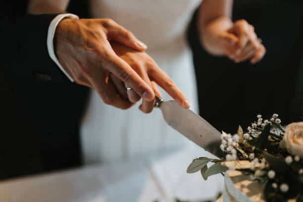 photo of a bride and a groom cutting a cake stock photo