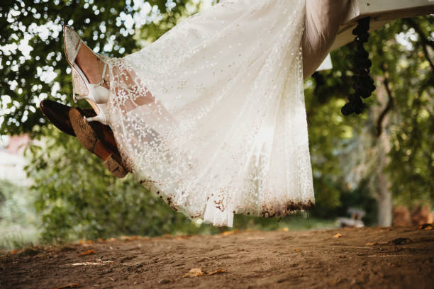 photo of a bride and a groom on a swing stock photo