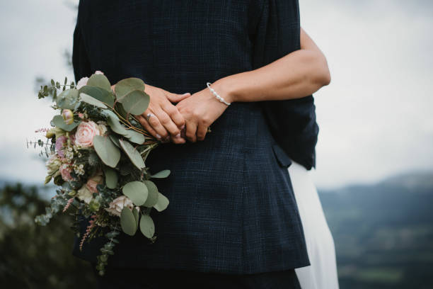photo of a bride with bouquet and the groom in the garden stock photo