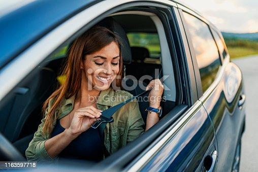 Young attractive woman sitting on car seat and fastening seat belt, car safety concept. Photo of beautiful young woman fastens a seat belt in the car - outdoors. Brown hair woman fastening seat belt in the car, safety concept. Business lady, Caucasian woman driver fastening car seat belt while sitting behind the wheel car. Safe driving concept. Selective focus, copy space