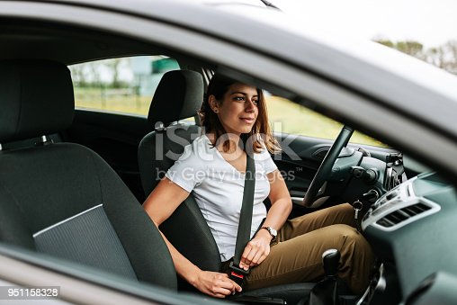 Photo of a business woman sitting in a car putting on her seat belt.