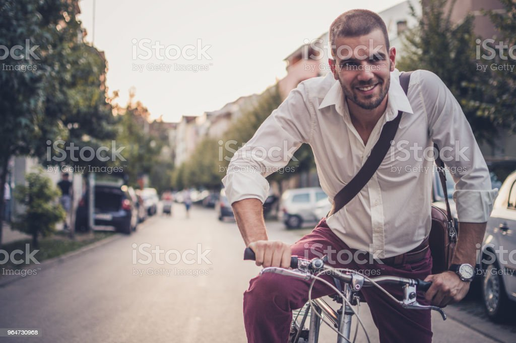 Photo of a businessman cycling home from his job royalty-free stock photo