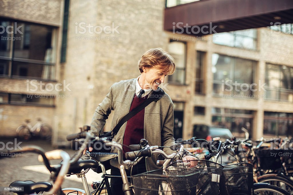 Photo of a businessman parking his bicycle stock photo