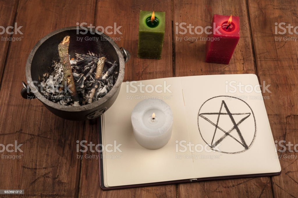 A photo of a candle, a witch's cauldron, and a pentacle in a book of shadows stock photo
