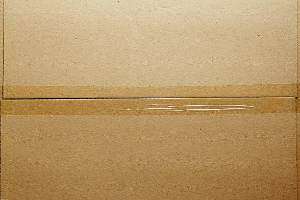 photo of a cardboard box taped at the middle - adhesive tape stock photos and pictures