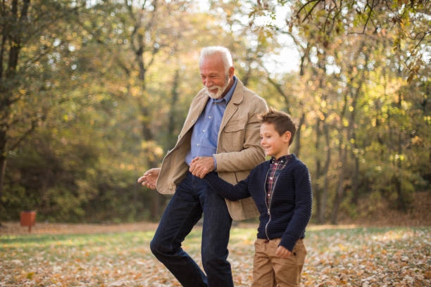 Photo of a cheerful grandfather and his grandson playing outdoors Photo of grandfather and his grandson in the park. 65 69 years stock pictures, royalty-free photos & images