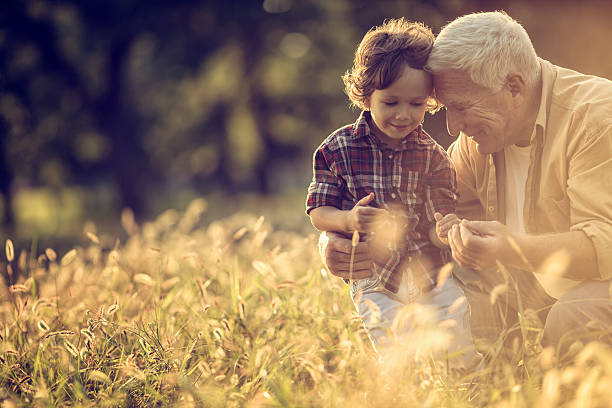 Photo of a cheerful grandfather and his grandson playing outdoors stock photo