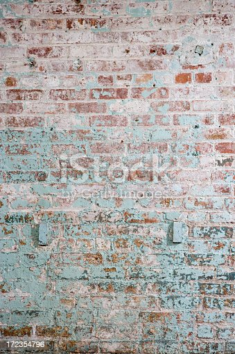 An interior, red brick wall that has been painted numerous times, most recently with white and then green paint.