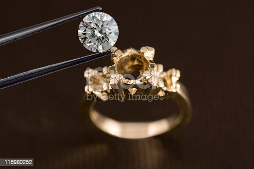 A diamond being examined before being set into an engagement ring OR a diamond being removed from an engagement ring.