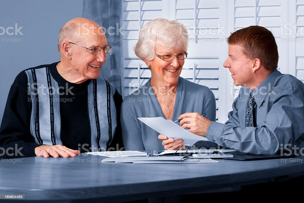 A photo of a financial advisor talking to an elderly couple stock photo