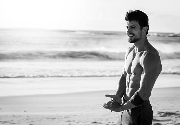 photo of a fit man enjoying the break after workout black and white photo of a strong fit man taking a break after hard workout,beautiful weather,sunny day,in the background waves splashing on the beach male animal stock pictures, royalty-free photos & images