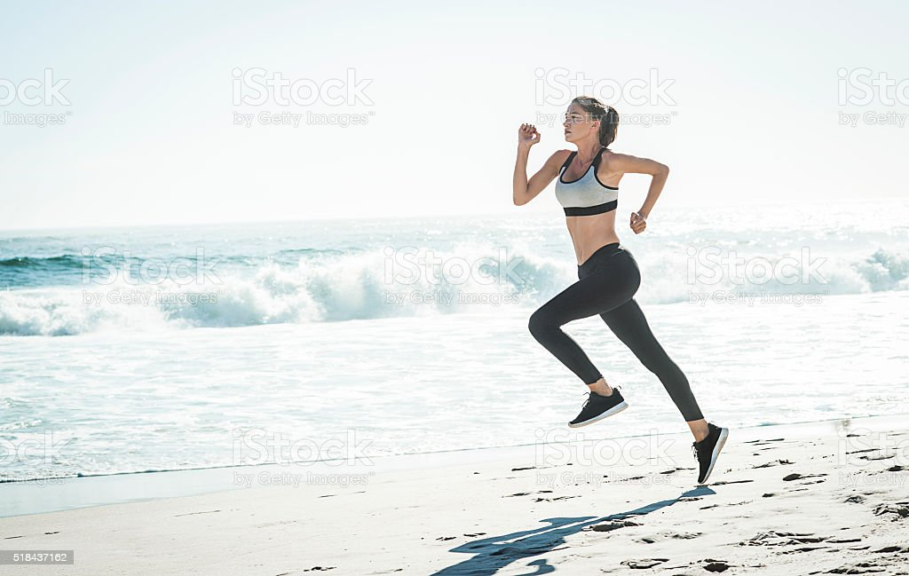 photo of a fit woman running on the beach stock photo