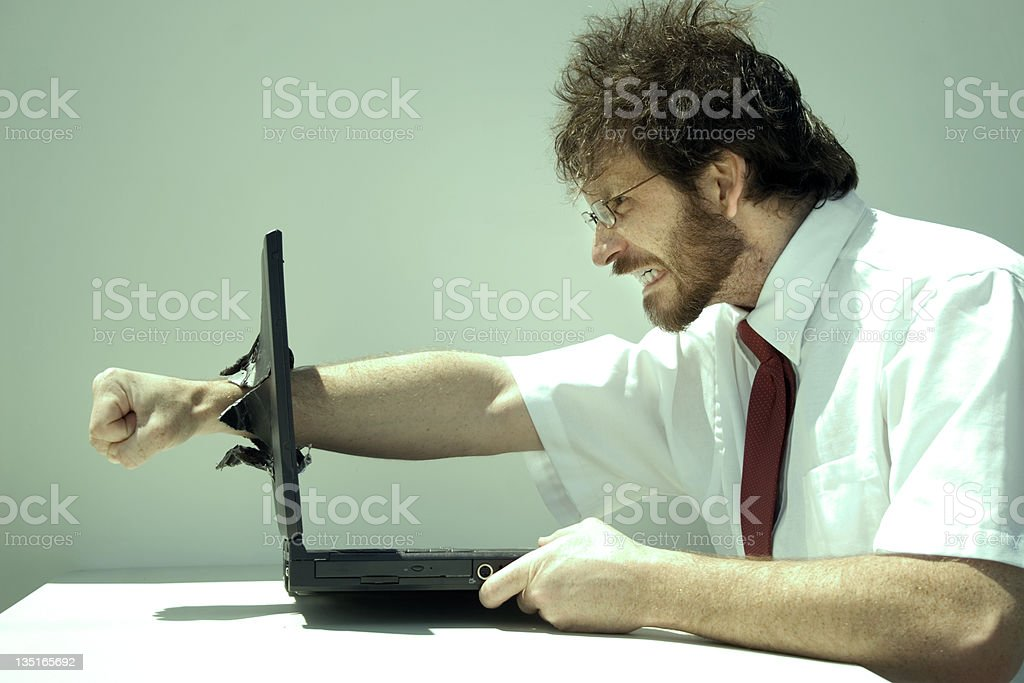 Photo of a frustrated man punching clean through his laptop stock photo