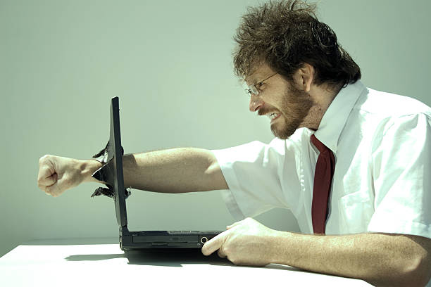 photo of a frustrated man punching clean through his laptop - punching stock photos and pictures