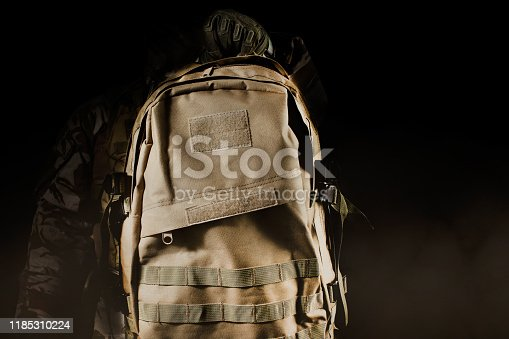 istock Photo of a fully equipped soldier in uniform holding backpack. 1185310224