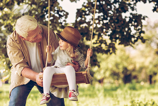 istock Photo of a grandfather and his granddaughter on swing 504189660
