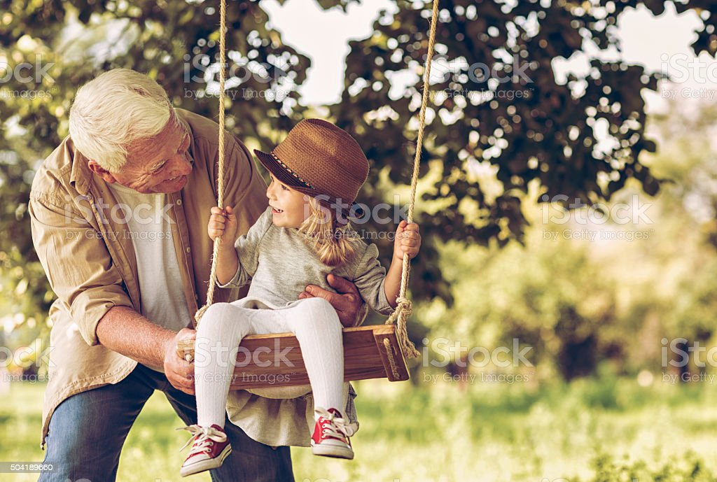 Photo of a grandfather and his granddaughter on swing stock photo