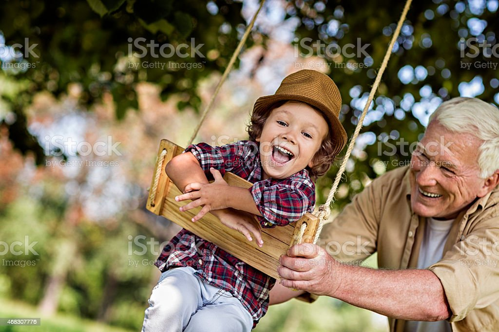 Photo of a grandfather and his grandson on swing stock photo