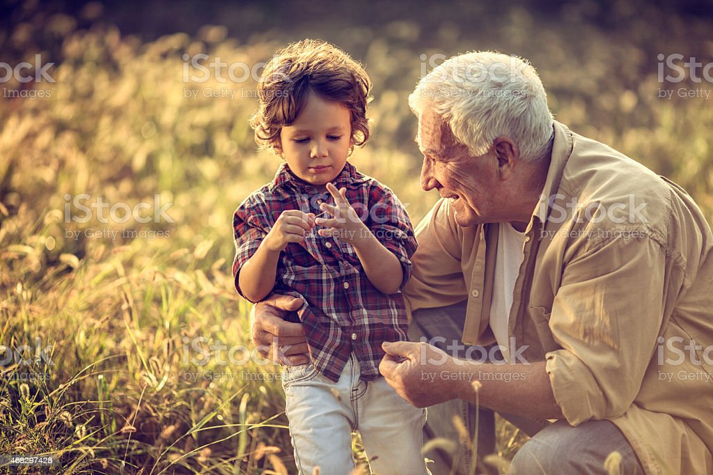 Photo of a grandfather outdoors with his grandson stock photo