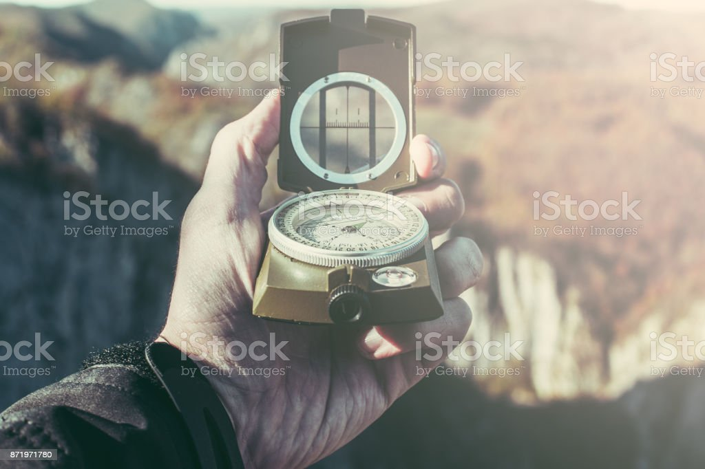 Photo of a hand holding a compass stock photo