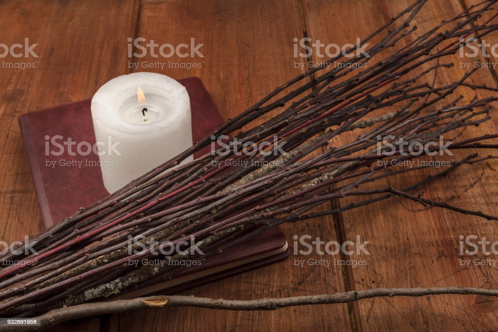 A photo of a handmade broom with a candle, a grimoire, and copy space stock photo